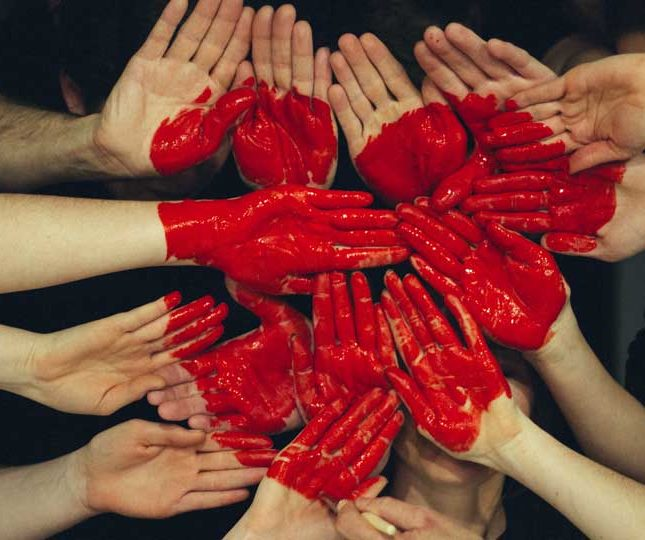 multiple hands with painted heart