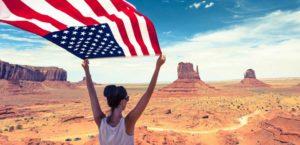 woman holding usa flag in desert