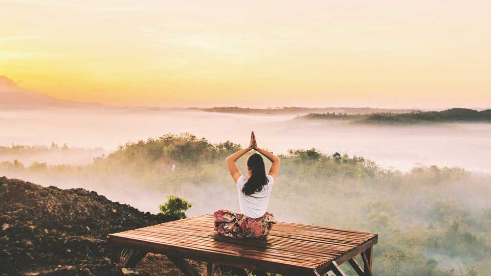Woman doing a yoga pose on mountain top