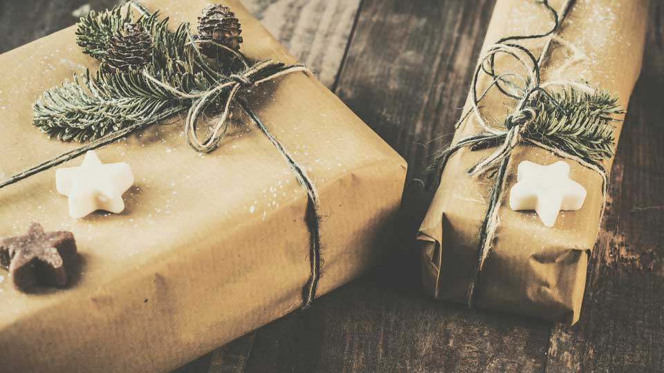 Holiday gifts wrapped in brown paper with holiday decorations