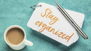 Coffee cup, pen and stay organized note on green table