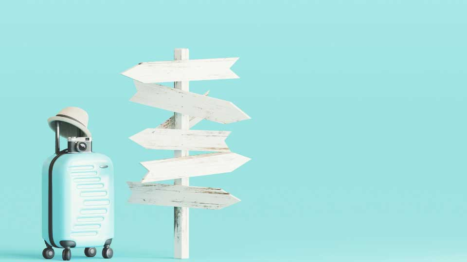 Blue suitcase and hat, camera with signpost on pastel blue background