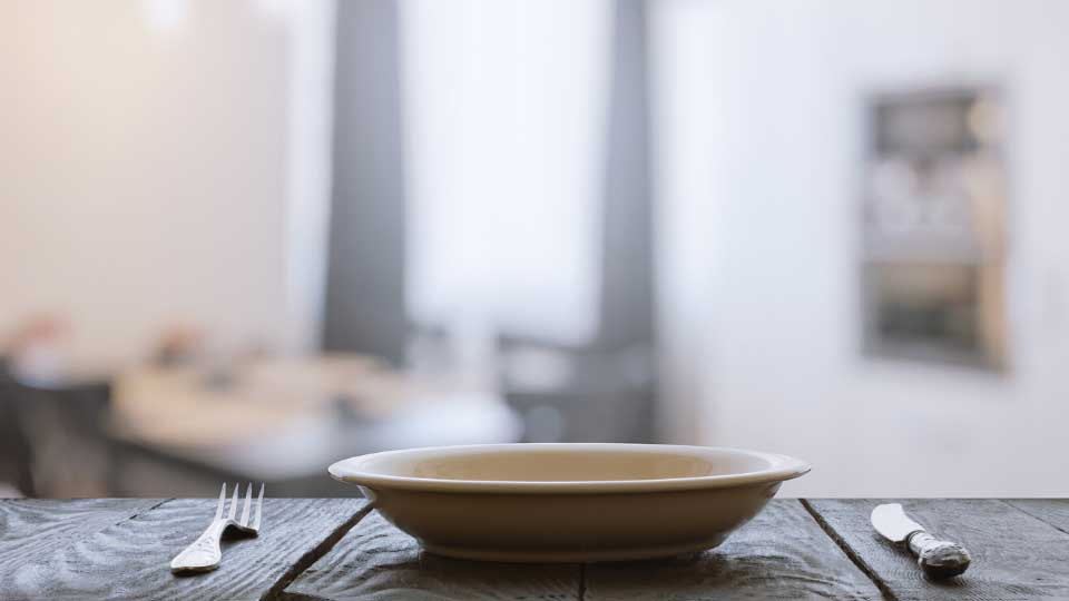 empty plate with fork and knife on wooden table