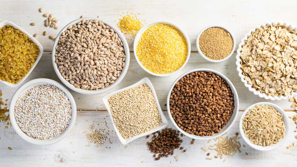 Different types of legumes and cereals on white background, top view. Organic grains
