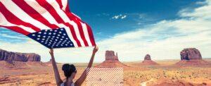 woman holding american flag in desert