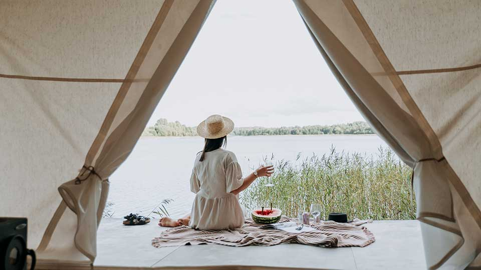 1. woman with white dress under a tent looking at a lake
