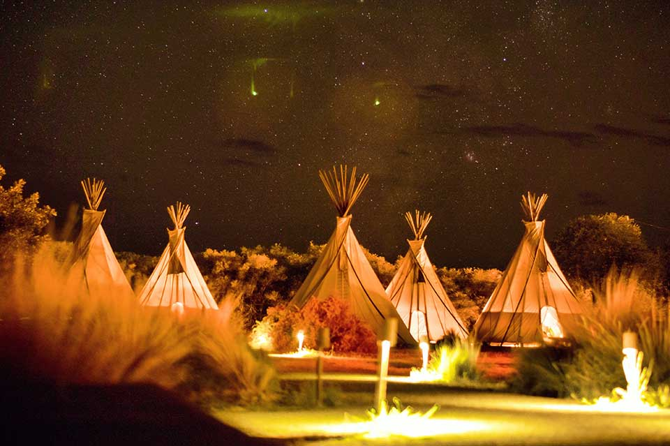 4. tipi tents with campfire in the background