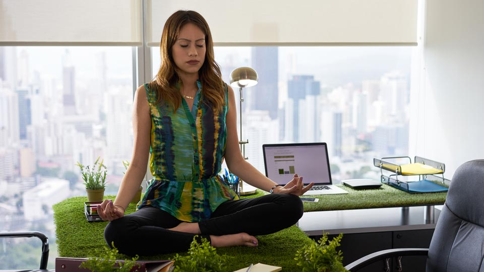 A person sitting on a desk meditating