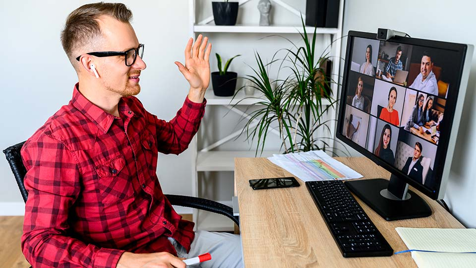 A young cheerful man greets with a gesture his coworkers in online video meeting, he sits at the office desk, a shelf with plants is on the background